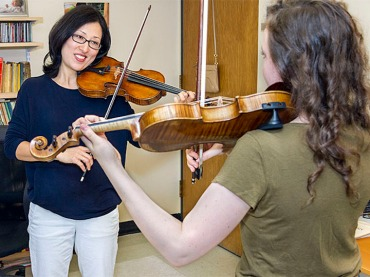 Altino (left), with freshman violinist Lydia Schweitzer, has developed a specialty in addressing overuse injuries.